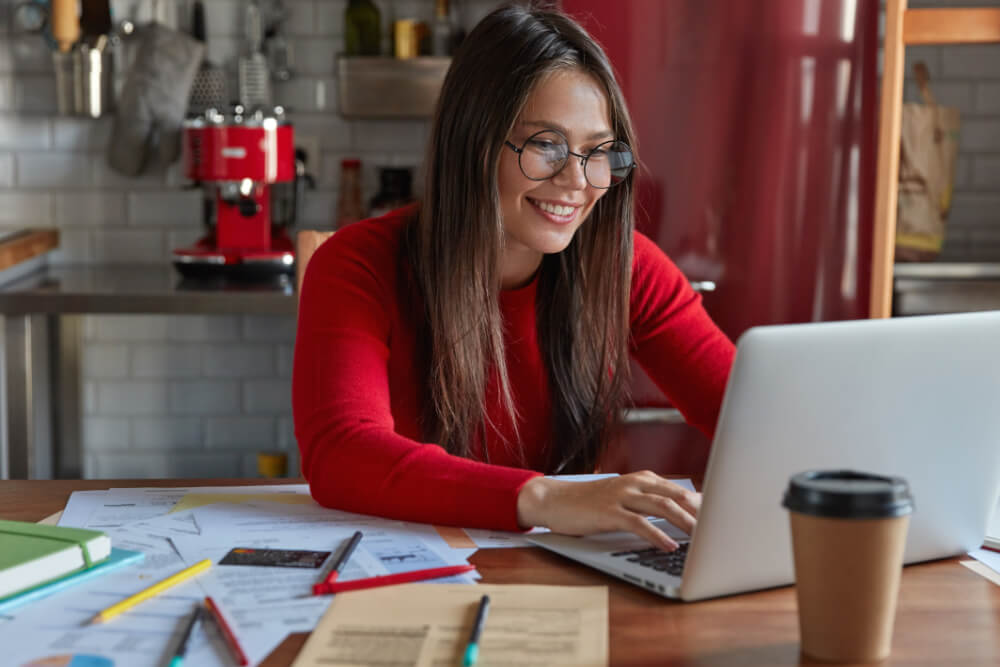 wirtualne biuro - co to? Zdjęcie przedstawia kobietę pracującą zdalnie z domu.